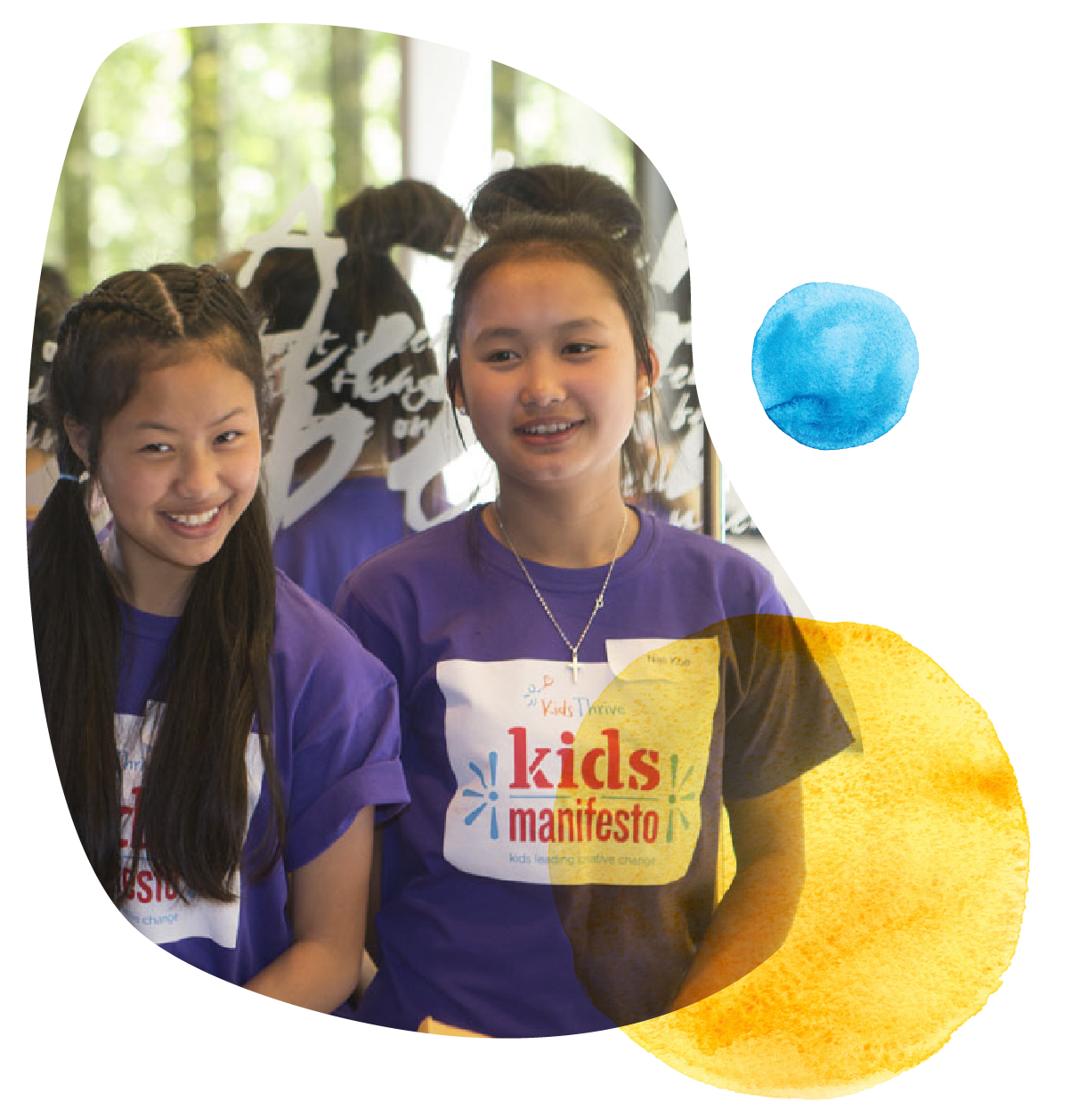 Two young women smiling with t-shirts saying Kids Manifesto